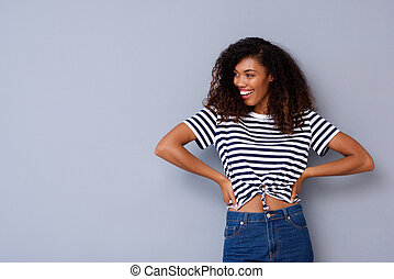 attractive young african woman smiling against gray background