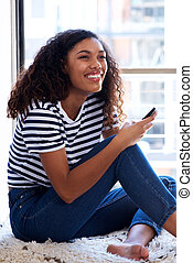 attractive young african woman smiling with cellphone