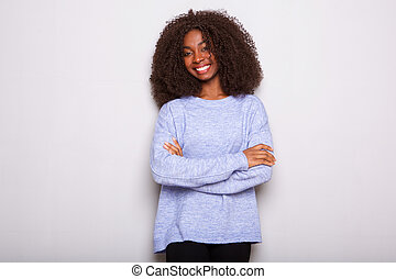 attractive young african woman standing against white background with arms crossed