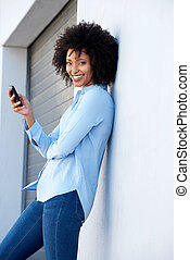 attractive young african woman with mobile phone leaning to wall outdoors