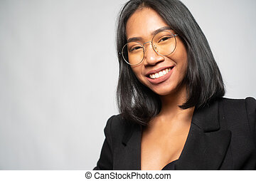 Portrait of attractive young Asian smiling woman in elegant black blazer and glasses