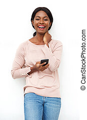 attractive young black woman laughing with cellphone against white background