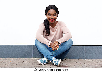 attractive young black woman sitting on floor and smiling against white wall