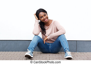attractive young black woman sitting on floor and smiling