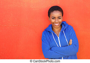 attractive young black woman smiling against red background