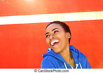 attractive young black woman smiling against red wall