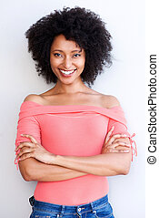 attractive young black woman standing with arms crossed and smiling against white background