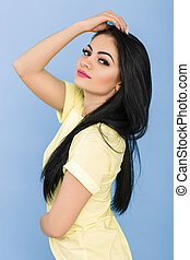 portrait of attractive young brunette woman in yellow dress on blue background.