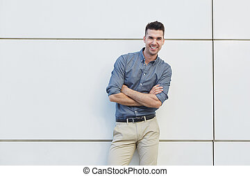 attractive young business man standing with arms crossed