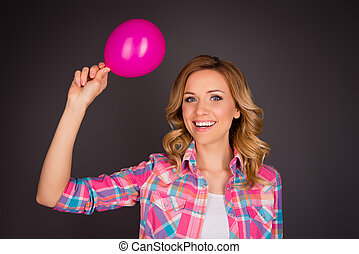 Portrait of attractive young girl holding pink balloon