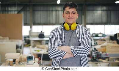Portrait of attractive young joiner standing in workshop...