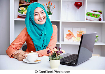 attractive young muslim woman enjoying a cup of tea while...
