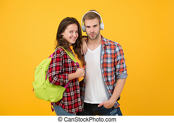 Portrait of attractive young students couple. cheerful woman wearing backpack. guy in headphones. online education concept. back to school. Couple of students abroad. study abroad concept. at campus
