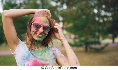 Portrait of attractive young woman covered with colorful paint at Holi festival smiling, looking at camera and touching her hair standing in park outdoors.