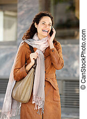 attractive young woman in coat and scarf talking on cell phone