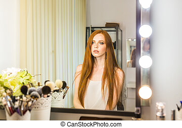 Portrait of attractive young woman looks in the mirror