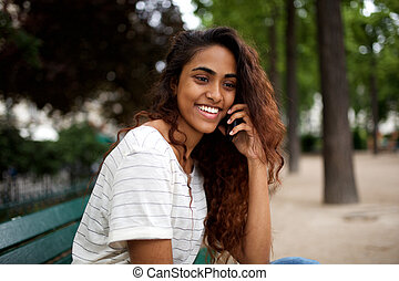 attractive young woman sitting in park and talking with cellphone