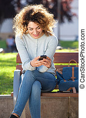 attractive young woman sitting on park bench looking at cellphone