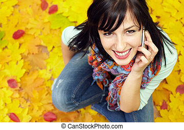 portrait of attractive young woman talking on the mobile phone and sitting on a carpet of yellow and red fallen leaves