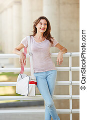 attractive young woman traveler smiling with bag