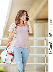 attractive young woman with bag talking on mobile phone
