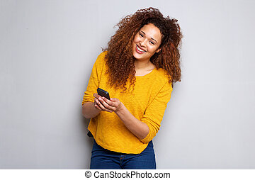 attractive young woman with curly hair holding cellphone