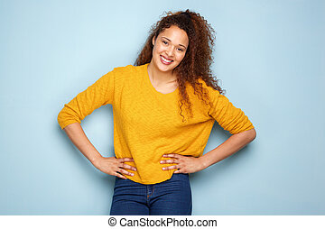 attractive young woman with curly hair smiling against gray background