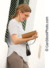 attractive young woman writing in book
