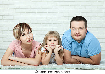 Portrait of baby and her parents lying on carpet in living room