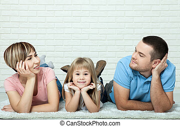 Portrait of baby and her parents lying on carpet in living room. White brick wall background, space for text.