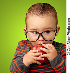 Portrait Of Baby Boy Eating Red Apple