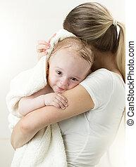 Portrait of baby boy hugging mother after having bath