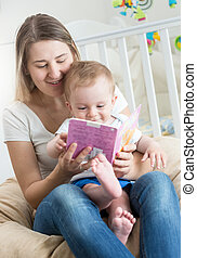 Portrait of baby boy sitting on mothers lap and reading book