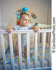 Portrait of baby boy standing in crib at night