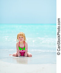 Portrait of baby girl sitting on sea coast