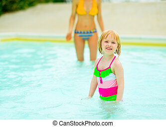 Portrait of baby girl with mother in swimming pool