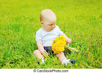 Portrait of baby with yellow dandelion flowers sitting on the grass in sunny summer day