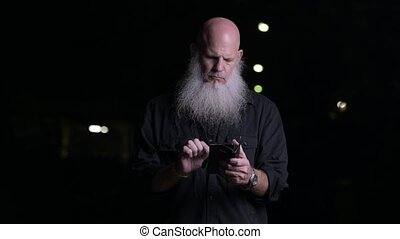 Portrait Of Bald Man With Beard Using Mobile Phone Outdoors At Night