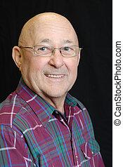 portrait of bald senior man with bright happy smile