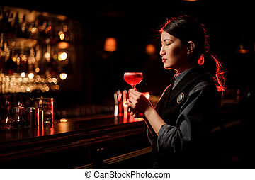 Portrait of bartender holding cocktail at the bar counter