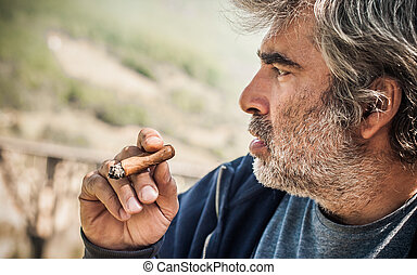 Portrait of bearded caucasian man smoking a cigar