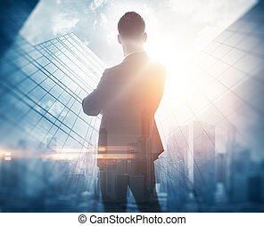 Stylish businessman in a suit looking at the horizon. Photo of double exposure of the city. Horizontal