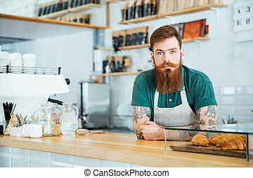 Portrait of bearded male barista standing in coffee shop -...