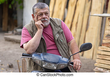 Portrait of bearded senior man sitting on a scooter and being in melancholy