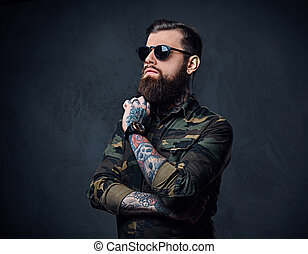 Portrait of bearded tattooed hipster male dressed in a ...
