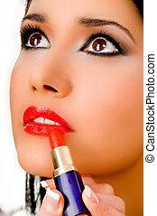 portrait of beautician applying lipsticks on female's lips ...