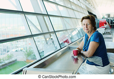 Portrait of beautiful 70 years old woman sitting in the airport