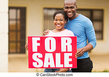 african american couple outside home with for sale sign