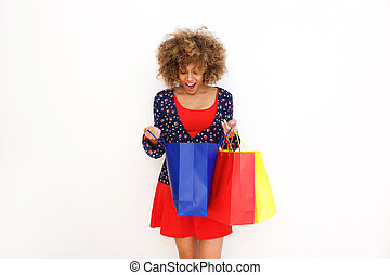 beautiful african american girl looking into shopping bag with surprised expression on face