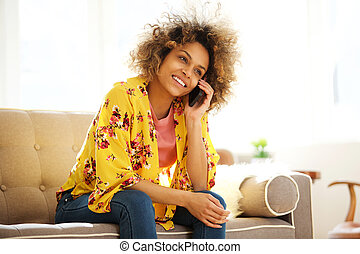 beautiful african american girl sitting on couch talking on cellphone
